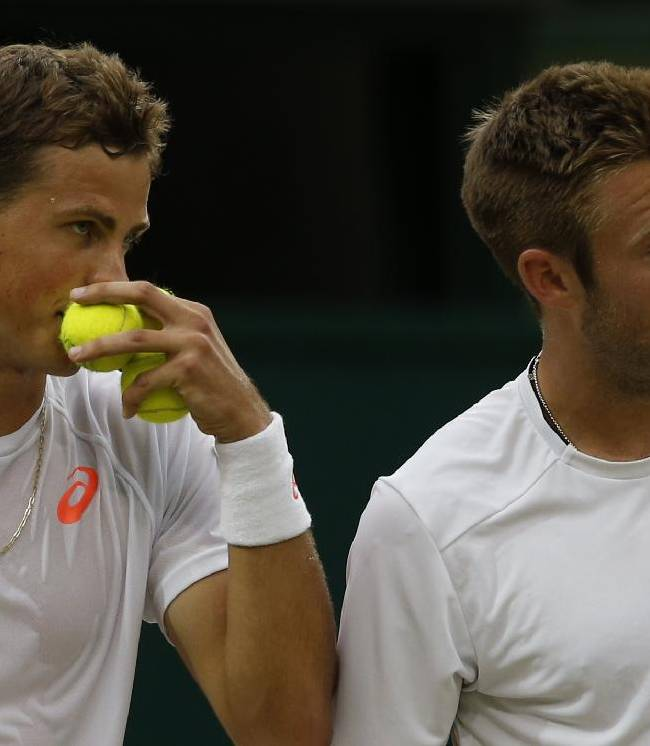 Vasek Pospisil of Canada, left, and Jack Sock of the U.S talk between points during the men's doubles final against Bob Bryan and Mike Bryan of the U.S at the All England Lawn Tennis Championships in Wimbledon, London, Saturday, July 5, 2014