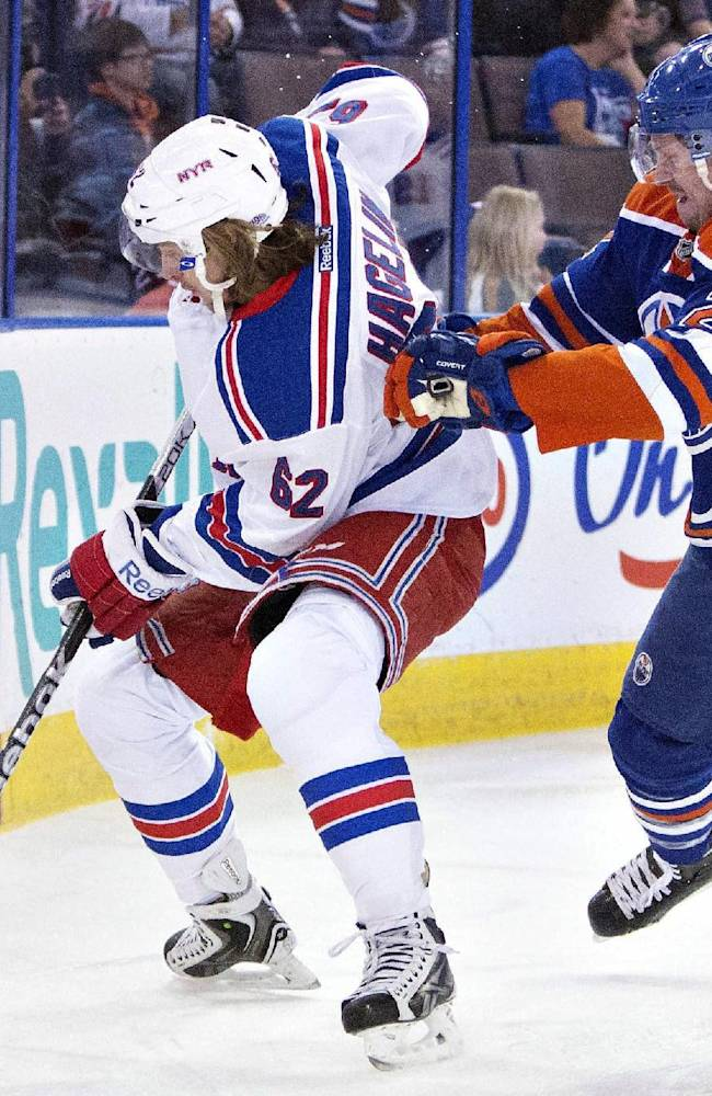 New York Rangers Carl Hagelin (62) battles with Edmonton Oilers Jeff Petry (2) during first period NHL hockey action in Edmonton, Alberta., on Sunday March 30, 2014