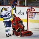 Vancouver Canucks' Chris Higgins, left, celebrates his team's goal as Calgary Flames goalie Jonas Hiller, from Switzerland, picks himself up during first period NHL hockey action in Calgary, Alberta, Wednesday, Oct. 8, 2014 The Associated Press