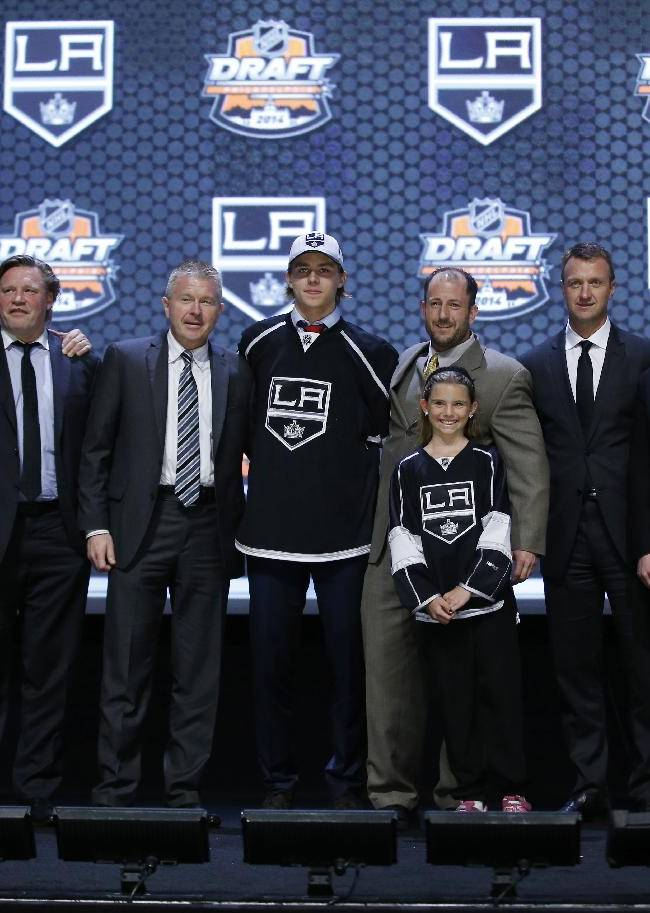 Adrian Kempe stands with Los Angeles Kings officials after being chosen 29th overall during the first round of the NHL hockey draft, Friday, June 27, 2014, in Philadelphia