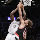 Portland Trail Blazers center Robin Lopez (42) tries to block Brooklyn Nets power forward Reggie Evans (30) as Evans goes up for a layup in the first half of their their NBA basketball game at the Barclays Center, Monday, Nov. 18, 2013, in Brooklyn The As