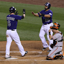 Colorado Rockies' Corey Dickerson, left, is congratulated after hitting a two-run home run by teammate Wilin Rosario, back right, as San Francisco Giants catcher Buster Posey looks down in the third inning of a baseball game in Denver on Monday, April 21,