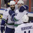 Vancouver Canucks' Nicklas Jensen, top right, of Denmark, celebrates with teammate Jason Garrison, left, and Alexandre Burrows (14) after scoring a goal during the first period of an NHL hockey game against the Florida Panthers, Sunday, March 16, 2014, in Sunrise, Fla. (AP Photo/Luis M. Alvarez)