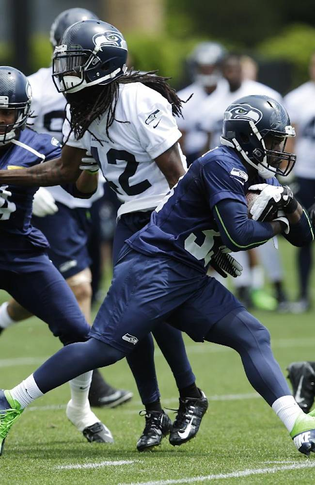 Seattle Seahawks running back Christine Michael second from right, carries the ball during a practice drill at an NFL football organized team activity, Monday, June 9, 2014 in Renton, Wash