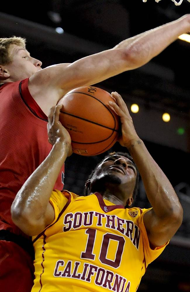 Utah center Dallin Bachynski (31) attempts to block Southern California guard Pe'Shon Howard (10) as he goes up for a shot during the second half of an NCAA college basketball game, Thursday, Feb. 13, 2014, in Los Angeles. Utah won 79-71