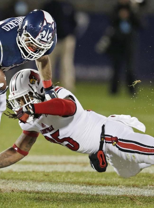 Louisville safety Calvin Pryor, right, dives as he tries to tackle Connecticut running back Max DeLorenzo (44) during the first half of an NCAA college football game, in East Hartford, Conn., Friday, Nov. 8, 2013