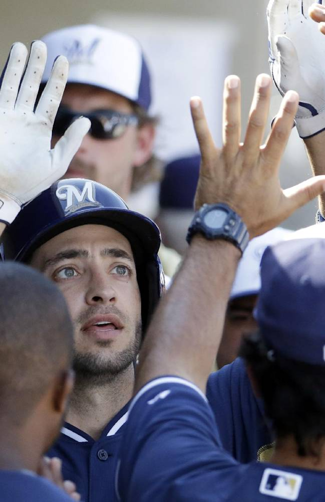 Milwaukee Brewers' Ryan Braun is congratulated by teammates after hitting a home run during the eighth inning of an exhibition baseball game against the Oakland Athletics on Wednesday, March 5, 2014, in Phoenix