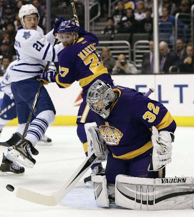 Los Angeles Kings goalie Jonathan Quick, center, makes a save as Toronto Maple Leafs' James van Riemsdyk (21) and  Kings' Alec Martinez (27) watch during the first period of an NHL hockey game on Thursday, March 13, 2014, in Los Angeles