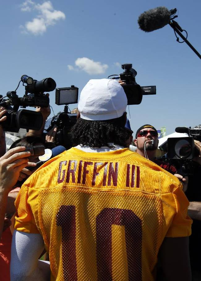 Washington Redskins quarterback Robert Griffin III talks with the media after practice at the team's NFL football training facility, Friday, July 25, 2014 in Richmond, Va. (AP Photo)