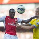 Arsenal's Yaya Sanogo, left, fights for the ball with Crystal Palace's Brede Hangeland during their English Premier League soccer match, at Emirates Stadium, in London, Saturday, Aug. 16, 2014