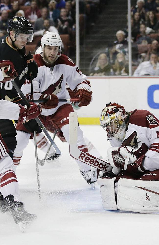 Phoenix Coyotes goalie Mike Smith (41) stops a shot in front of Coyotes' Keith Yandle (3), Derek Morris (53), and Anaheim Ducks' Corey Perry (10) during the second period of an NHL hockey game on Friday, Oct. 18, 2013, in  Anaheim, Calif