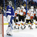 Tampa Bay Lightning goalie Ben Bishop (30) watches as the Calgary Flames celebrate a goal by Kevin Westgarth (15) during the first period of an NHL hockey game on Thursday, April 3, 2014, in Tampa, Fla The Associated Press
