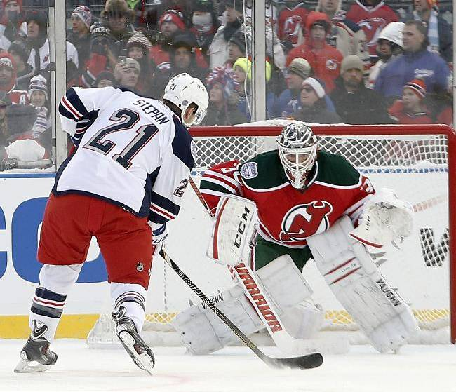 New York Rangers center Derek Stepan (21) takes a penalty shot against New Jersey Devils goalie Martin Brodeur (30) in the third period of an NHL outdoor hockey game at Yankee Stadium in New York, Sunday, Jan. 26, 2014. The Rangers won 7-3