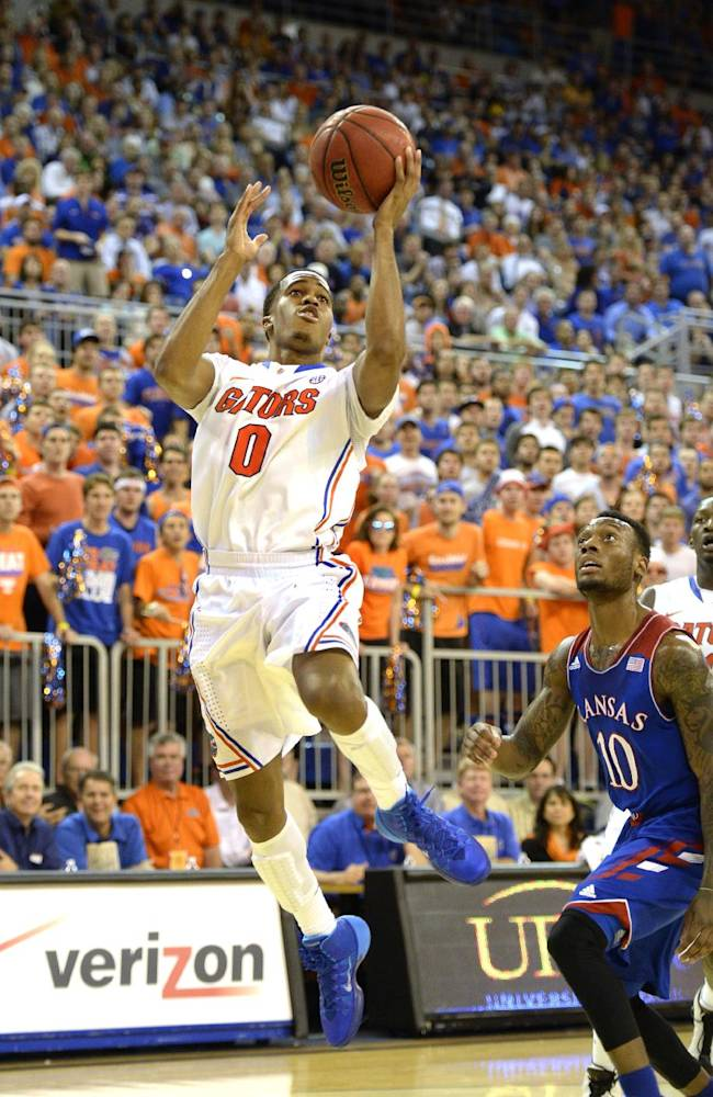 Florida guard Kasey Hill (0) goes for the basket with Kansas guard Naadir Tharpe (10) unable to block the shot during the first half of an NCAA college basketball game Tuesday, Dec. 10, 2013 in Gainesville, Fla. Florida took the win over The University of Kansas 67-61