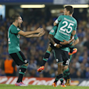 Schalke's scorer Klaas Jan Huntelaar, right, jumps on teammate Dennis Aogo and is celebrated by Marco Hoeger, left, after scoring during the Champions League Group G soccer match between Chelsea and Schalke 04 at Stamford Bridge stadium in London Wednesda