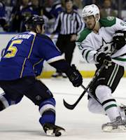 Dallas Stars' Tyler Seguin, right, passes around St. Louis Blues' Barret Jackman during the first period of an NHL hockey game Tuesday, March 11, 2014, in St. Louis. (AP Photo/Jeff Roberson)