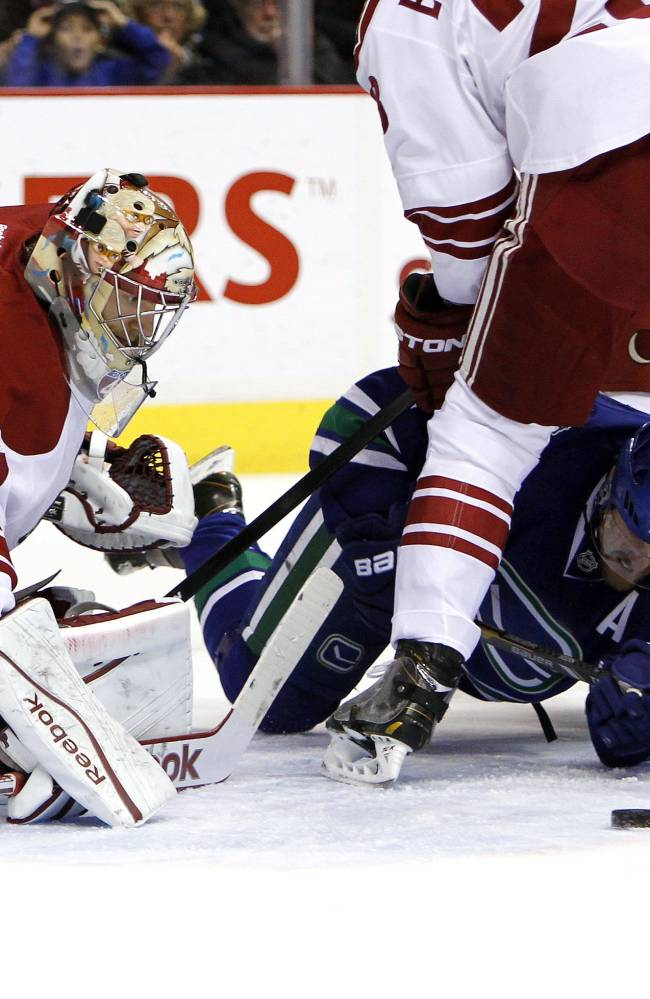 Vancouver Canucks' Daniel Sedin (22) tries to move the puck as he lies on the ice but is stopped by Phoenix Coyotes goaltender Mike Smith (41) during first period NHL hockey action in Vancouver, British Columbia, on Friday Dec. 6, 2013