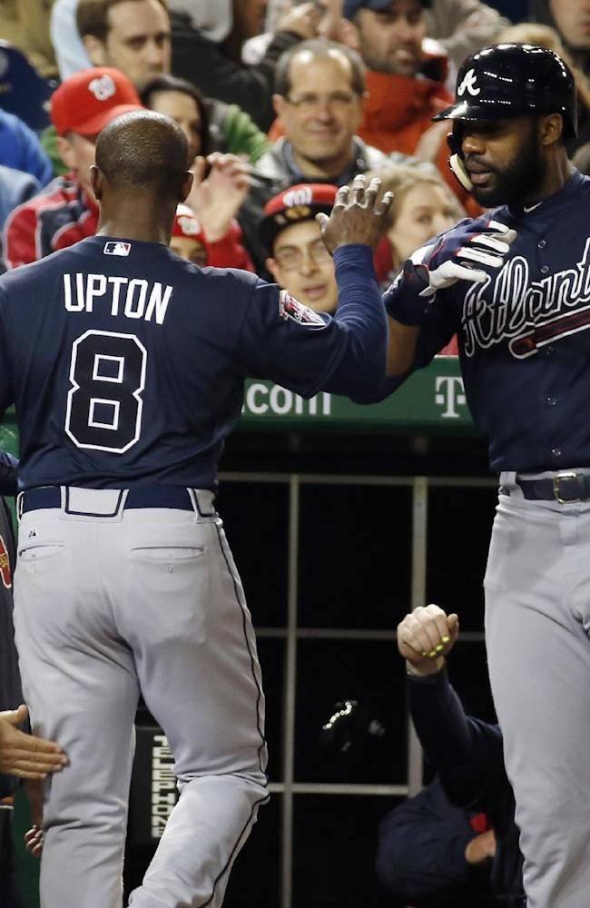 Atlanta Braves' Justin Upton (8) celebrates after scoring, with manager Fredi Gonzalez, left, and Jason Heyward during the fourth inning of a baseball game against the Washington Nationals at Nationals Park Saturday, April 5, 2014, in Washington. Upton scored on a throwing error by Nationals third baseman Ryan Zimmerman