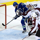 Vancouver Canucks' Ryan Kesler, left, scores a goal as Colorado Avalanche's Gabriel Landeskog, top right, of Sweden, goalie Jean-Sebastien Giguere and Andre Benoit, bottom right, watch during third period of an NHL hockey game in Vancouver, British Columb