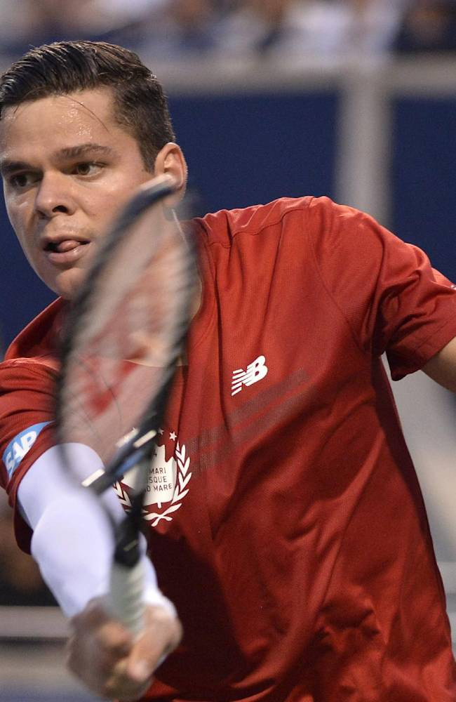 Milos Raonic, of Canada, retuns to Feliciano Lopez, of Spain, during the Rogers Cup tennis tournament in Toronto, Friday, Aug. 8, 2014