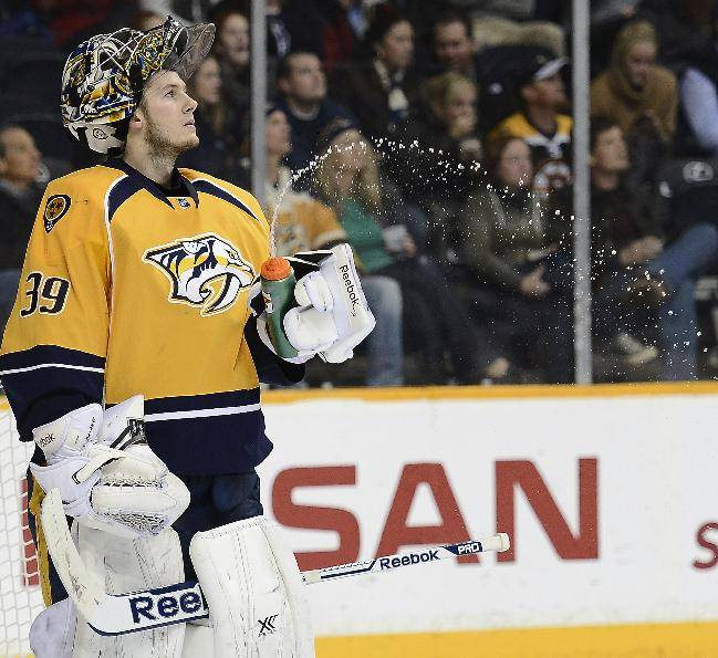 Nashville Predators goalie Marek Mazanec (39), of Czech Republic, squirts the water out of his bottle after the Boston Bruins scored a goal in the third period of an NHL hockey game on Monday, Dec. 23, 2013, in Nashville, Tenn. The Bruins won 6-2