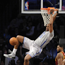 Brooklyn Nets' Jason Collins (98) hangs from the rim after dunking against the Cleveland Cavaliers in the second half of an NBA basketball game Friday, March 28, 2014, in New York. The Nets won 108-97 The Associated Press