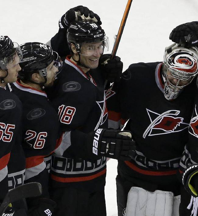 Carolina Hurricanes goalie Anton Khudobin, of Kazakhstan, is congratulated by Ron Hainsey (65), John-Michael Liles (26), Radek Dvorak (18), of the Czech Republic, and Nathan Gerbe following an NHL hockey game against the Columbus Blue Jackets in Raleigh, N.C., Monday, Jan. 27, 2014. Carolina won 3-2