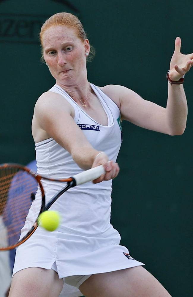 Alison Van Uytvanck of Belgium returns to Domimika Cibulkova of Slovakia during their women's singles match at the All England Lawn Tennis Championships in Wimbledon, London, Wednesday, June 25, 2014