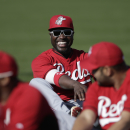 Cincinnati Reds second baseman Brandon Phillips, center, jokes during a spring training baseball workout Thursday, Feb. 20, 2014, in Goodyear, Ariz The Associated Press