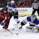 Washington Capitals center Nicklas Backstrom (19), from Sweden, works the puck in front of St. Louis Blues goalie Brian Elliott (1) as defenseman Barret Jackman (5) defends, in the first period of an NHL hockey game, Sunday, Feb. 1, 2015, in Washington Th