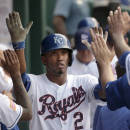 Kansas City Royals' Alcides Escobar celebrates in the dugout after scoring on a two-run triple by Lorenzo Cain during the fifth inning of a baseball game against the Minnesota Twins on Saturday, July 4, 2015, in Kansas City, Mo. (AP Photo/Charlie Riedel)