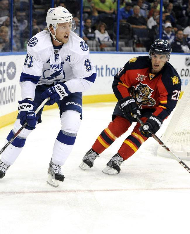 Tampa Bay Lightning center Steven Stamkos, left, controls the puck in front of Florida Panthers defenseman Mike Mottau during the second period of a preseason NHL hockey game Saturday, Sept. 21, 2013, in Tampa, Fla