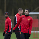 Manchester United's Robin van Persie, right, smiles as he trains with teammates at Carrington training ground in Manchester, Monday, Feb. 24, 2014. Manchester United will play Olympiakos in a Champions League first knockout round on Tuesday