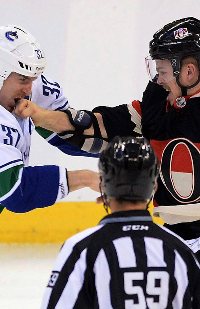 Ottawa Senators' Mark Borowiecki, right, lands a punch to the face of Vancouver Canucks' Dale Weise during first-period NHL hockey game action in Ottawa, Ontario, Thursday, Nov. 28, 2013