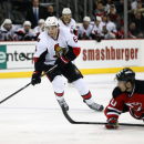 New Jersey Devils defenseman Peter Harrold (10) falls to the ice as Ottawa Senators right wing Bobby Ryan (6) skates with the puck during the first period of an NHL hockey game, Tuesday, Feb. 3, 2015, in Newark, N.J The Associated Press