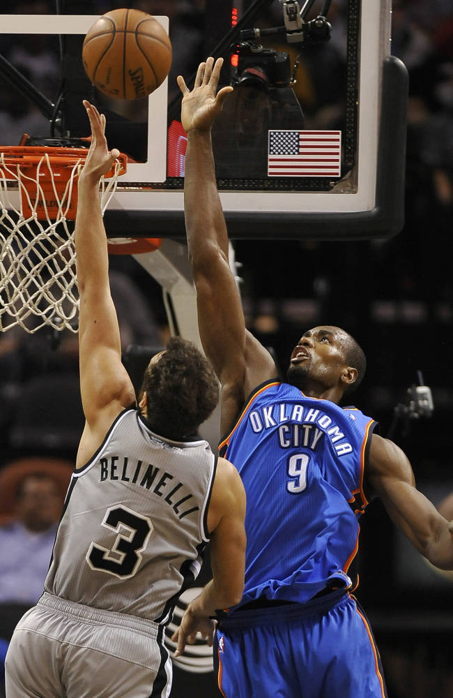 Oklahoma City Thunder forward Serge Ibaka, right, defends San Antonio Spurs guard Marco Belinelli, of Italy, during the second half of an NBA basketball game, Saturday, Dec. 21, 2013, in San Antonio. Oklahoma City won 113-100