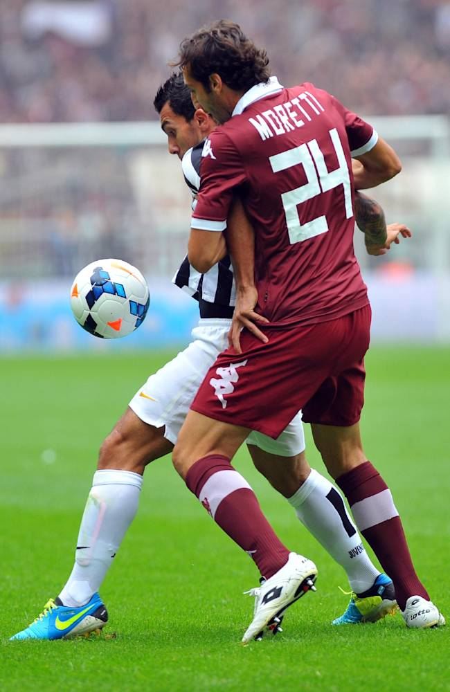 Juventus forward Carlos Tevez, of Argentina, left, is challenged by Torino's Emiliano Moretti during a Serie A soccer match between Torino and Juventus at the Olympic stadium, in Turin, Italy, Sunday, Sept. 29, 2013