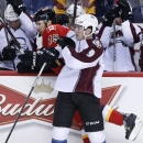 Colorado Avalanche's Matt Duchene, right, hits Calgary Flames' David Jones in front of the Colorado bench during first-period NHL hockey game action in Calgary, Alberta, Thursday, Dec. 4, 2014 The Associated Press