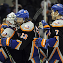 New York Islanders' Colin McDonald (13) and Matt Carkner (7) congratulate goalie Evgeni Nabokov (20) after the Islanders shut out the Columbus Blue Jackets 2-0 in an NHL hockey game on Sunday, March 23, 2014, in Uniondale, N.Y The Associated Press