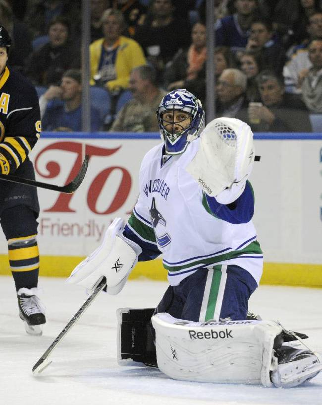 Buffalo Sabres' Steve Ott (9) and Vancouver Canucks' Roberto Luongo (1) watch a shot miss the net during the first period of an NHL hockey game in Buffalo, N.Y., Thursday, Oct. 17, 2013
