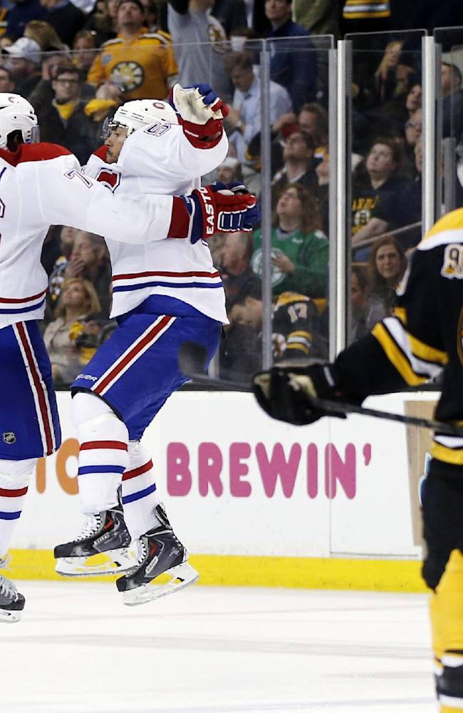Montreal Canadiens defenseman Francis Bouillon jumps with defenseman P.K. Subban (76) to celebrate his goal as Boston Bruins center David Krejci, right, skates away during the third period in Game 1 of an NHL hockey second-round playoff series in Boston, Thursday, May 1, 2014