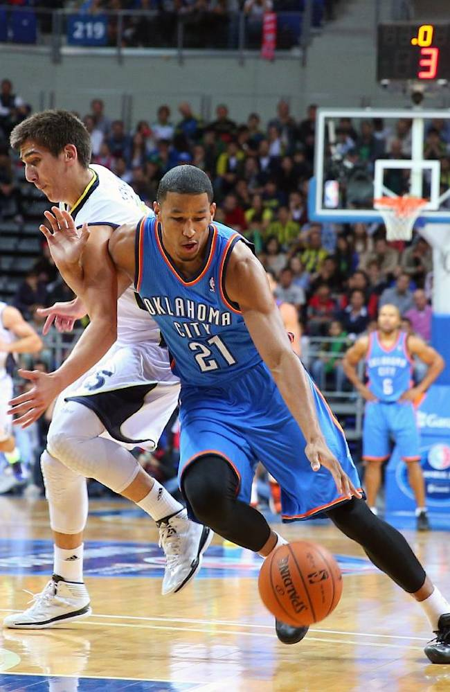 The NBA team Oklahoma City Thunder's Andre Roberson, right,  as Kenan Sipahi of Fenerbahce Ulker defends during a basketball game in Istanbul, Turkey, Saturday, Oct. 5, 2013. Oklahoma City Thunder has opened the preseason schedule with a game against the  five-time Turkish champions at the Ulker Sports Arena. (AP Photo)