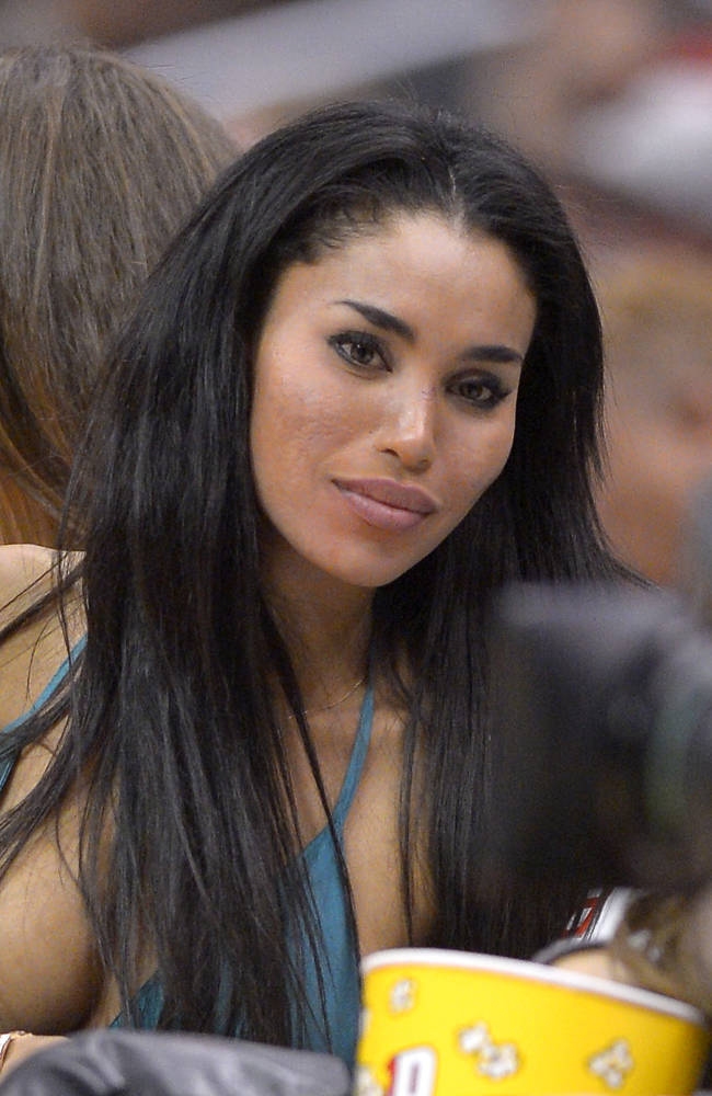 An Oct. 25, 2013, file photo is of V. Stiviano watching the Los Angeles Clippers play the Sacramento Kings during the first half of an NBA basketball game in Los Angeles.  Stiviano, the woman Los Angeles Clippers owner Donald Sterling was talking to when he made racist remarks says she was assaulted by two men outside a New York City hotel Sunday June 1, 2014