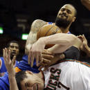 New York Knicks' Tyson Chandler, top, and Milwaukee Bucks' Ersan Ilyasova (7) battle for a rebound during the first half of an NBA basketball game on Wednesday, Dec. 18, 2013, in Milwaukee. (AP Photo/Morry Gash)