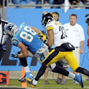 Carolina Panthers' Greg Olsen (88) dives into the end zone for a touchdown as Pittsburgh Steelers' Mike Mitchell (23) pursues during the second half of an NFL football game in Charlotte, N.C., Sunday, Sept. 21, 2014 The Associated Press