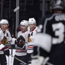 Chicago Blackhawks right wing Patrick Kane, second from left, celebrates his goal with teammates defenseman Duncan Keith, left, and left wing Patrick Sharp, second from right, as Los Angeles Kings goalie Jonathan Quick watches during the first period of a