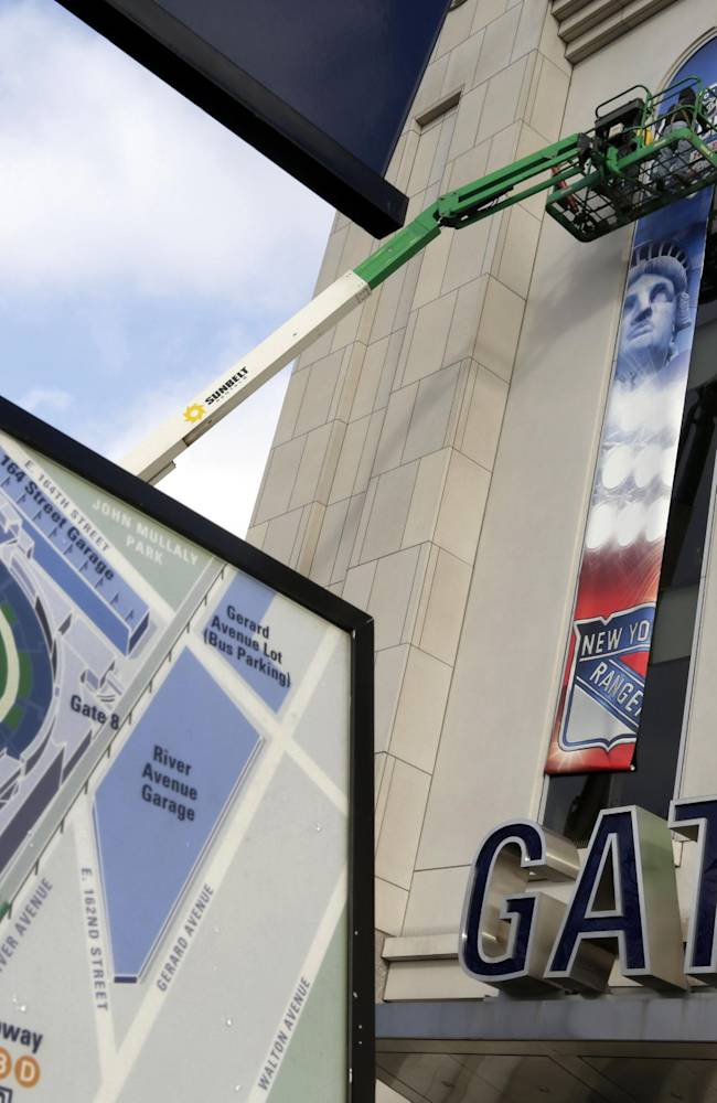 Workers hang banners outside New York's Yankee Stadium, Saturday, Jan. 18, 2014 for NHL Stadium Series games.  The stadium will host the New York Rangers and New Jersey Devils on Jan. 26 and the Rangers-New York Islanders on Jan. 29