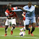 Arsenal's Bacary Sagna, left, vies for the ball with Manchester City's Yaya Toure during the English Premier League soccer match between Arsenal and Manchester City at the Emirates stadium in London, Saturday, March 29, 2014