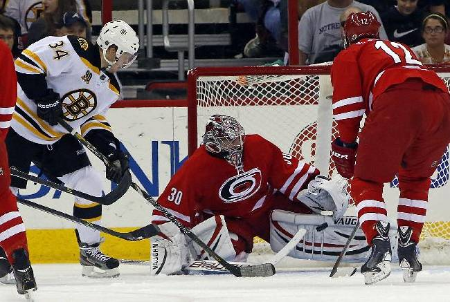 Carolina Hurricanes goalie Cam Ward (30) blocks the shot of Boston Bruins' Carl Soderberg (34) of Germany, with Hurricanes' Eric Staal (12) looking on during the second period of an NHL hockey game in Raleigh, N.C., Monday, Nov. 18, 2013