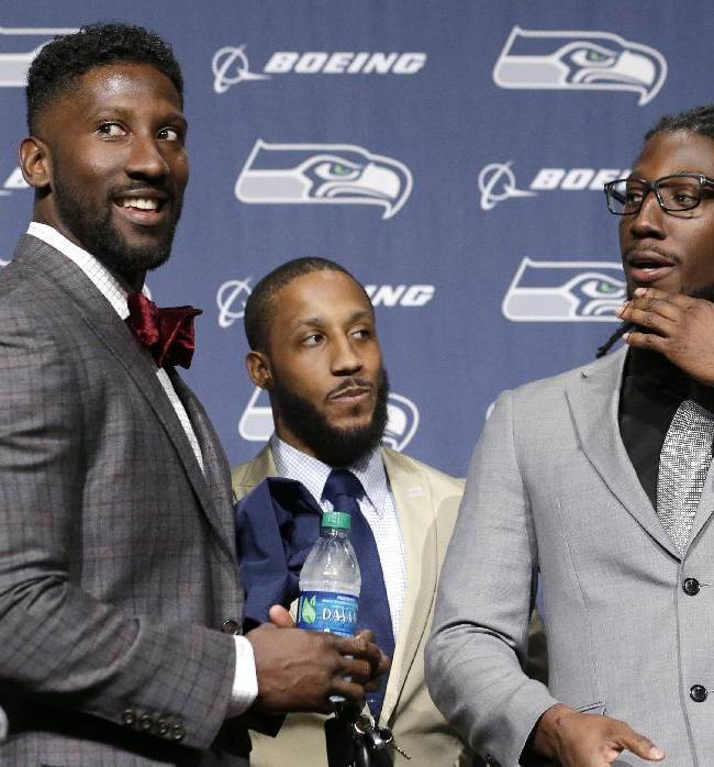Seattle Seahawks' Marcus Trufant, left, is joined by his brothers Isaiah, center, and Desmond after a news conference announcing his retirement from football after signing with the team a day earlier, Thursday, April 24, 2014, in Renton, Wash. Marcus Trufant started 125 games in a Seattle career that lasted from 2003 to 2012. The cornerback was a first-round pick in 2003 out of Washington State and immediately moved into the starting lineup, playing a key role on the 2005 team that advanced to the franchise's first Super Bowl
